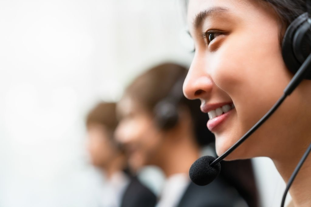stock photo... Save Side view of smiling woman consultant wearing microphone headset of customer support phone operator at workplace. Side view of smiling woman consultant wearing microphone headset of customer support phone operator at workplace. Call Center Stock Photo Description Side view of smiling woman consultant
