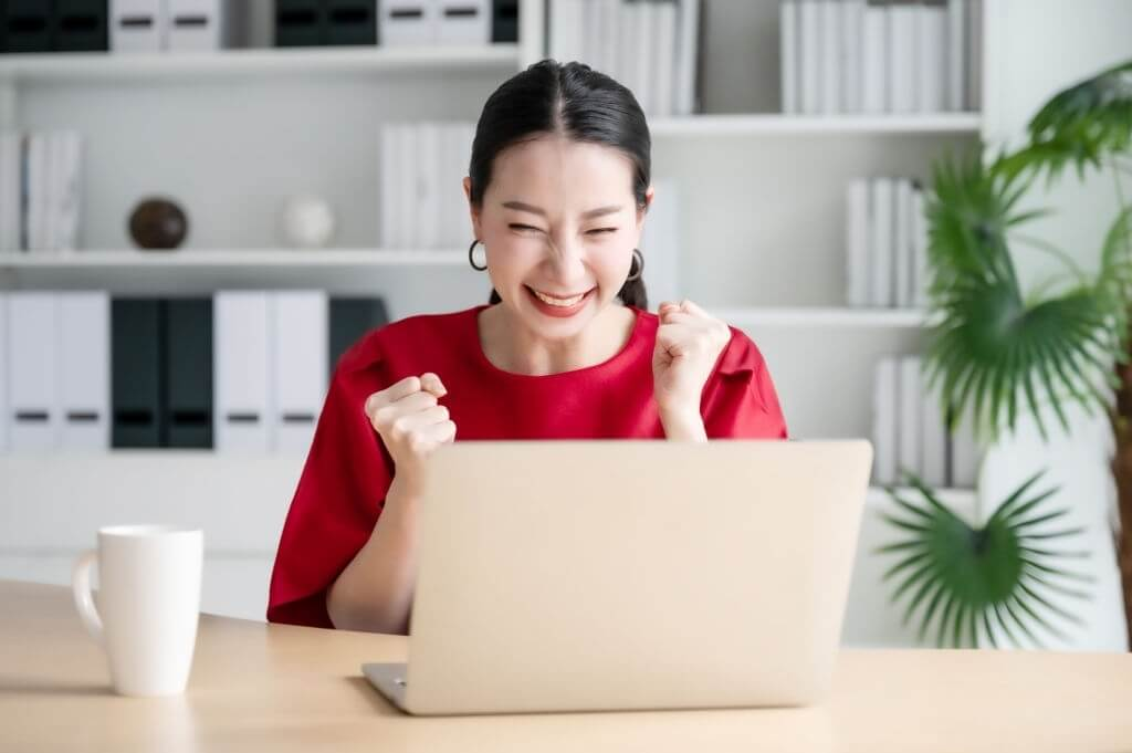 young woman happy about good email news